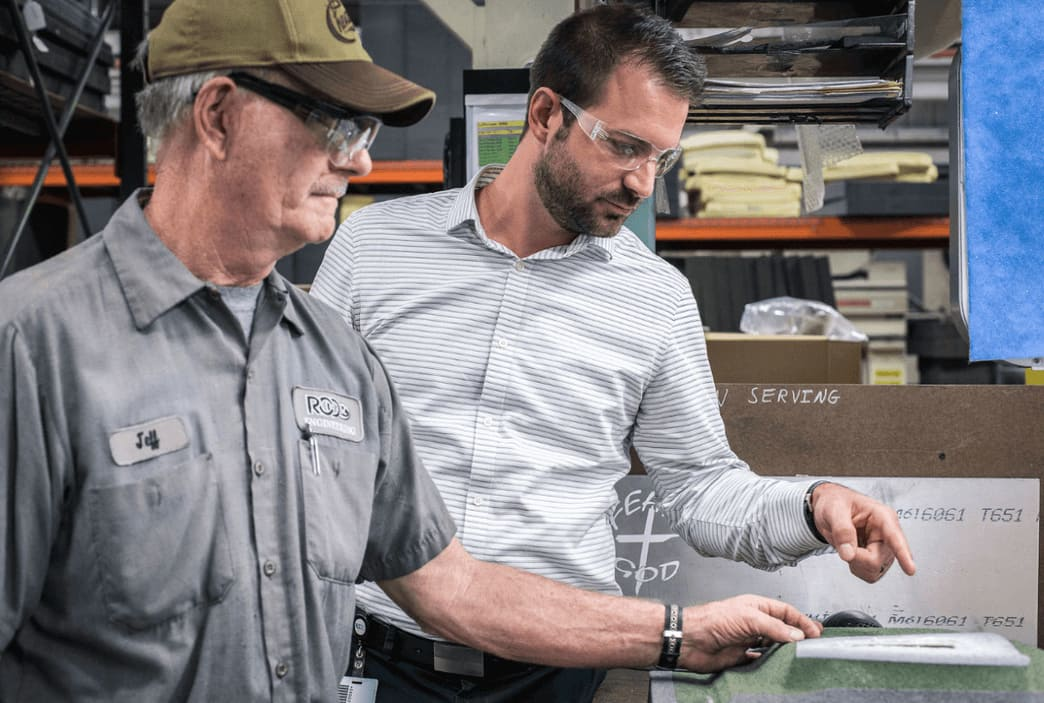 A man working with an engineer hired through contract manufacturing engineering services
