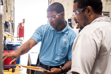 Two workers review a quality board in a plastic parts facility.
