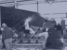 Workers building a mocked up full scale airplane fuselage made by rapid prototyping services
