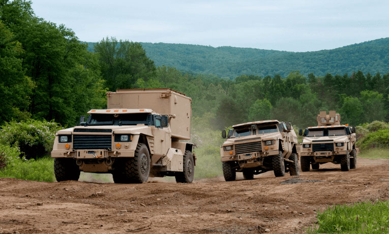 Prototype military vehicles driving through a mountain landscape.