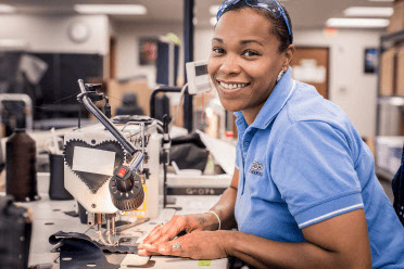 A seamstress smiles while sewing automotive leather seat covers.