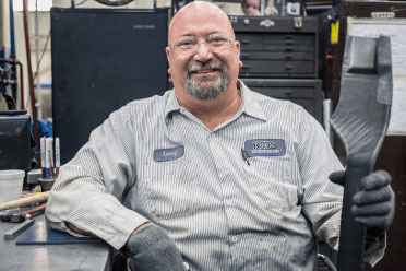 A sheet metal worker holds a part and smiles for the camera.